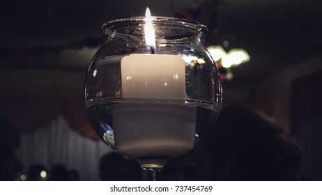 Candle in glass at Christmas dinner