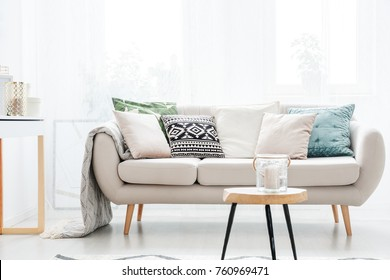 Candle in a glass jar on table in front of beige sofa with pillows in scandinavian style living room
