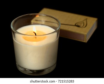 Candle in glass with matches in the black background.