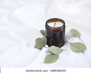 Candle in glass packaging decorated with eucalyptus leaves isolated on textured white background. Flat lay. Top view. Copy space