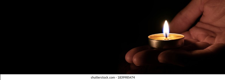 Candle in hand burning in the black background. Copy space. The concept of mourn, grief or mourning. You can use it as a banner.