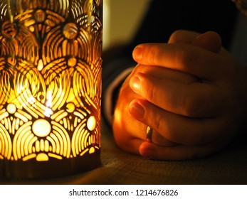 Candle and hands folded together in prayer or petition, the hands of an adult man with a wedding ring, thanksgiving