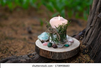 Candle with herbs surrounded by gems and crystals on the roots of an old tree: tiger's eye, malachite, rose quartz, white quartz, fluorite.