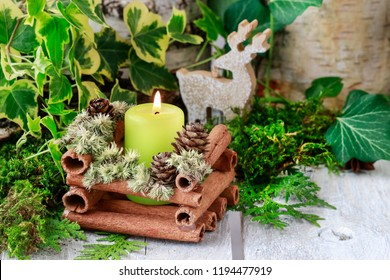 Candle holder made of cinnamon sticks and moss. Green Christmas decoration idea.
