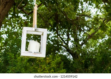 A candle inside a wooden rectangle, hanging with a rope on a tree, on the background of a farm's park in Puglia, Italy.