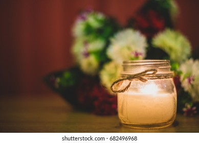 Candle in a jar in front of flower bouquet, decorative for bridal themes or sad occasions