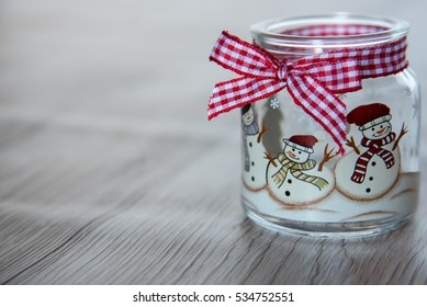 Candle jar with ribbon decorated with snowman on wooden surface