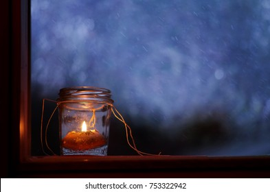 Candle in jar in the window and falling snow on background