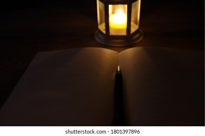 Candle Lantern, Blank Notebook And Pen Concept In Dark Atmosphere