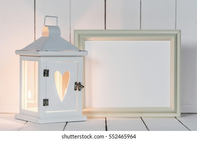 Candle lantern decorated with heart and picture frame on white wooden background