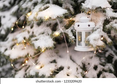 Candle lantern hanging from snowy tree branch at dusk. Christmas time.