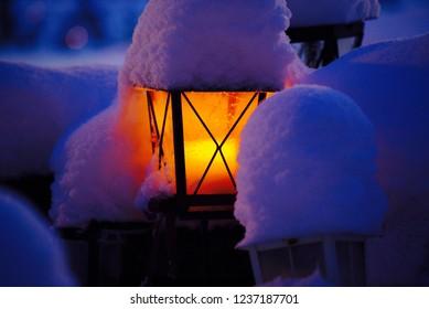 candle lantern / lamp in deep snowy landscape.