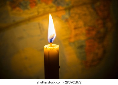 Candle light with  bur world globe  as a  background, copy space