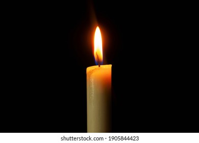 Candle light burning brightly in the black background.
