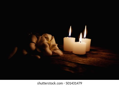 Candle light with frangipani flowers on wooden desk in black background soft focus(selective focus)
