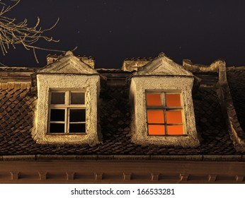 Candle light inside the room, seen on a window under a starry night