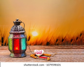 "Candle light lids on muslim style's lantern shining on arabic letter of the name of God ""Allah"" in heart shape, use as greeting on ramadan kareem mubarak"