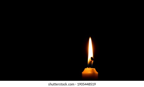 Candle light on black background. Burning candle in the dark. Space for text.