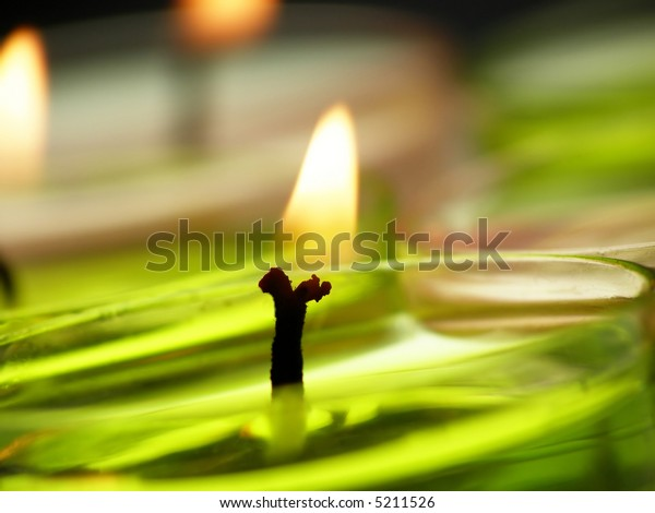 Candle light in soft pastel colors against white background
