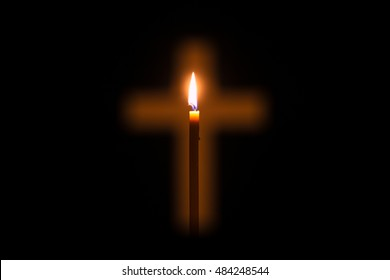 Candle is lighting and glowing through hole in shape of Christian cross among darkness. Light of faith is shining in darkness of unbelief. Concept of Christianity, religiosity and sincere faith