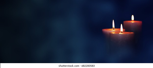Candle lights in blue darkness for contemplative moments