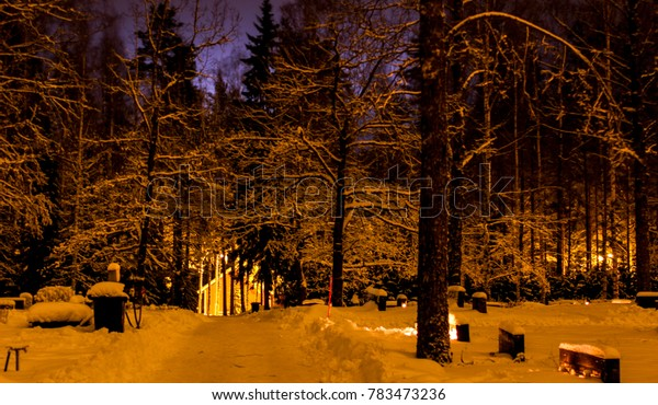 Candle lit snowy cemetery in Christmas time