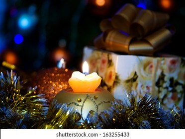 Candle on the background of the Christmas tree and gifts