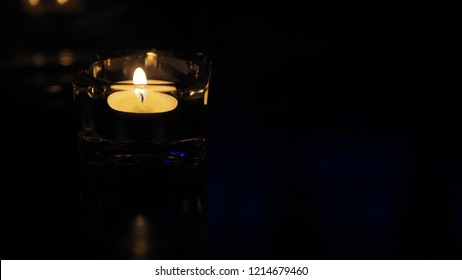 A candle on a black background, tealight on a table