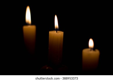 Candle on dark background. Candle in low key. Candle flame at night closeup.