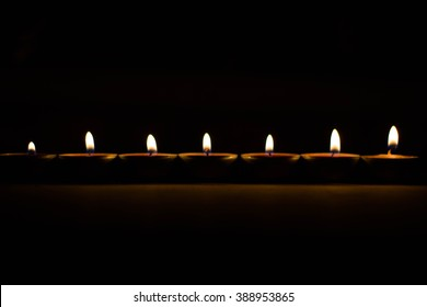 Candle on dark background. Candle on dark background. Small candles in a row, in one strip, in a line. Alight candles in a row on black background. Candle flame at night closeup.