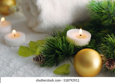 Candle on pine tree branch and Christmas decorations, closeup