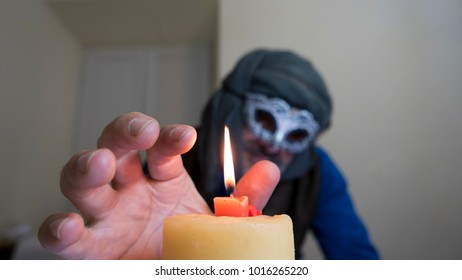 candle and out of focus mask , venetian carnival concept