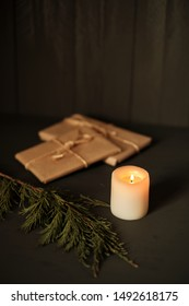 A candle with packages of gifts wrapped in kraft paper in the background