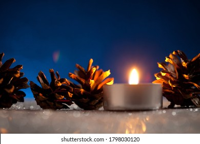 Candle and pinecones on dark blue background. On top of image is empty space to put text or something else. This file is cleaned and retouched.