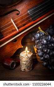 Candle, pipe, violin and red grape on wooden background