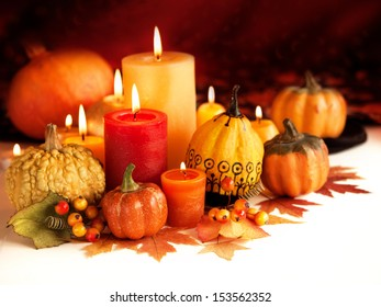 Candle and pumpkins on a autumn background