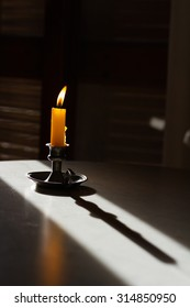 Candle in shadow