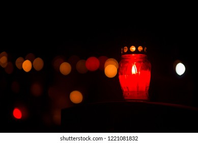 Candle snitch on the tombstone, the feast of the dead, All Saints' Day by night with bokeh colorful background. Copy space