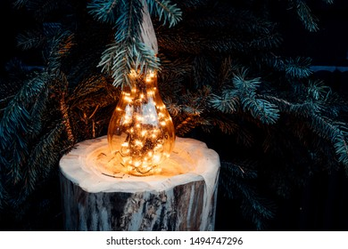 A candle stands on a block of wood and lit the Christmas market