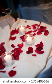 candle surrounded by rose petals