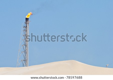 A candle tower burning off excess gas at an oil refinery in the desert.