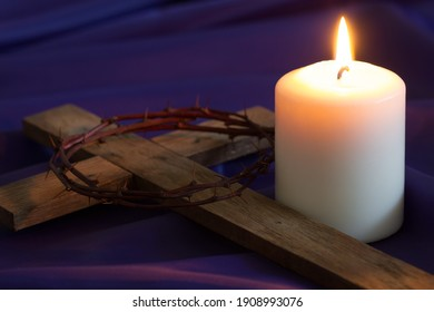 Candle and wooden cross with thorns on violet fabric background, concept