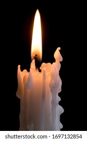 Candleflame on a lit candle.  White candle burning, isolated on a dark background