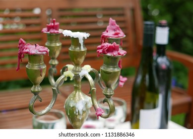 Candleholder with burnt out candles and wine bottles on table
