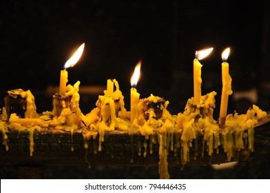 Candlelight from candle stick is shining in the dark background. Drops of melting wax coming from the burnt candle gives the old lonely scary feeling.