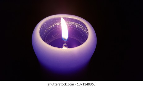 Candlelight flame closeup. Burning fire of single purple candle in darkness. Reflection of glowing flame in liquid wax of violet candle. Cylinder shape candle with round top closeup.
