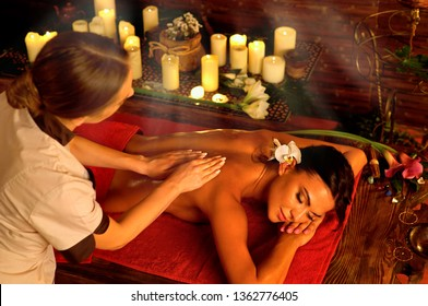 Candlelight massage of woman with masseuse with sun flare.