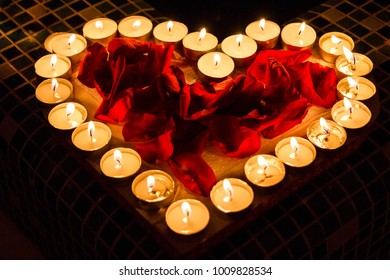 Candlelights shine in form of the heart with red roses petals