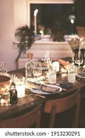 Candlelit dining table and chairs set up with glasses and tableware for an evening dinner party
