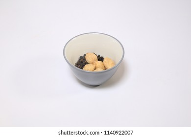 candlenut or called kemiri in Indonesian. black paper on bowl.  Seasoning food on isolated white background